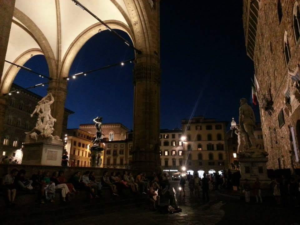 Escuchando música clásica sentados en el suelo de la plaza.