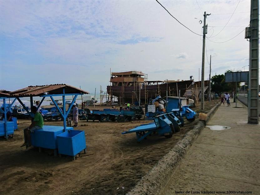 Barcos varados en la playa siendo reparados.